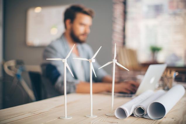 3 miniatyrer av vindkraftverk på ett bord